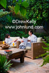 Luxury resort spa photo of a couple in white bathrobes sitting on a wooden bench in a lush tropical patio garden with glases of orange juice. The couple is smiling and happy.